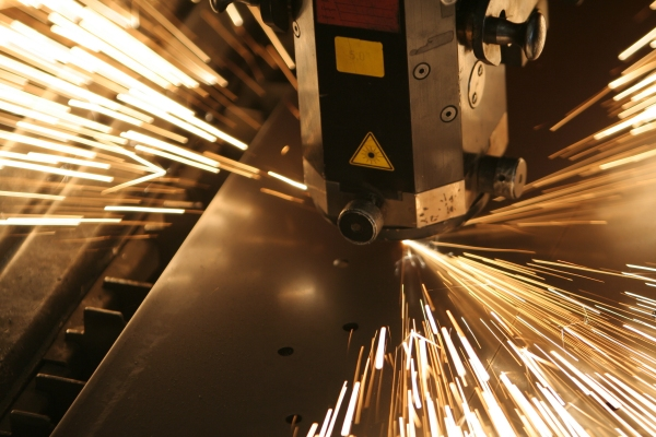Close up of a laser machine cutting metal with sparks shooting out from the side